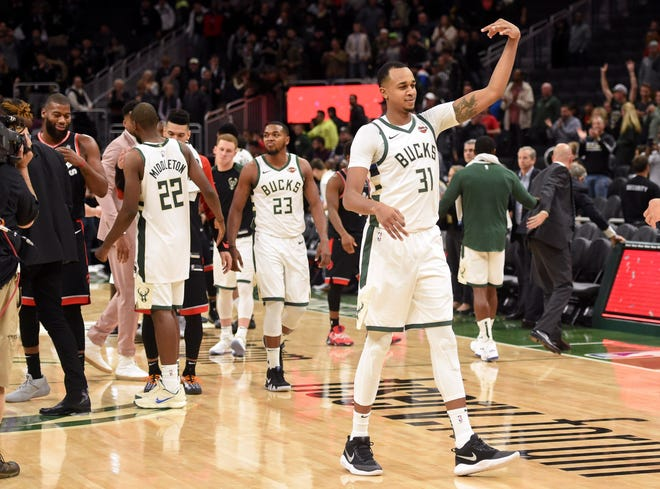 A happy John Henson walks off the court after the Bucks finished off the Raptors, 124-109, on Monday night at Fiserv Forum.