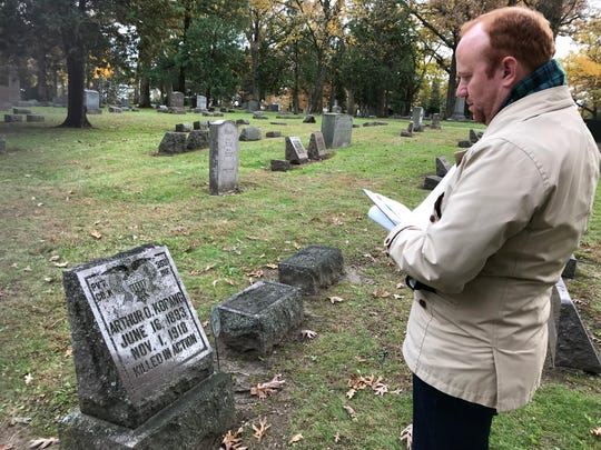 Kevin Hampton, curator of history at the Wisconsin Veterans Museum, checks the gravesite of Arthur O. Kopang who was killed in action in France one month after arriving in Europe to fight in World War I. Kopang is among at least a dozen soldiers killed on French battlefields who were returned to their hometown in Madison several years later for burial at Forest Hill Cemetery.