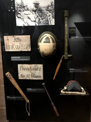 A display in the Wisconsin Veterans Museum of objects brought back from World War I by Wisconsin soldiers includes signs in German, a periscope used to peer above trenches, weapons and a German helmet. An exhibit on World War I at the Madison museum closes Dec. 29.