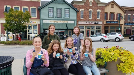 Girl Scout Cadettes Troop 4615 members (from top left to bottom right) Isabella Mailloux, Kelli Harrigan, Zoe Kohler, Elizabeth Kuhnen, Zoie Knisbeck and Colleen Hopkins sit outside the Pewaukee Chocolate Factory, one of two local businesses the Scouts were able to get involved with their project of sending care packages and reminders of home to Pewaukee military members stationed in the Middle East.