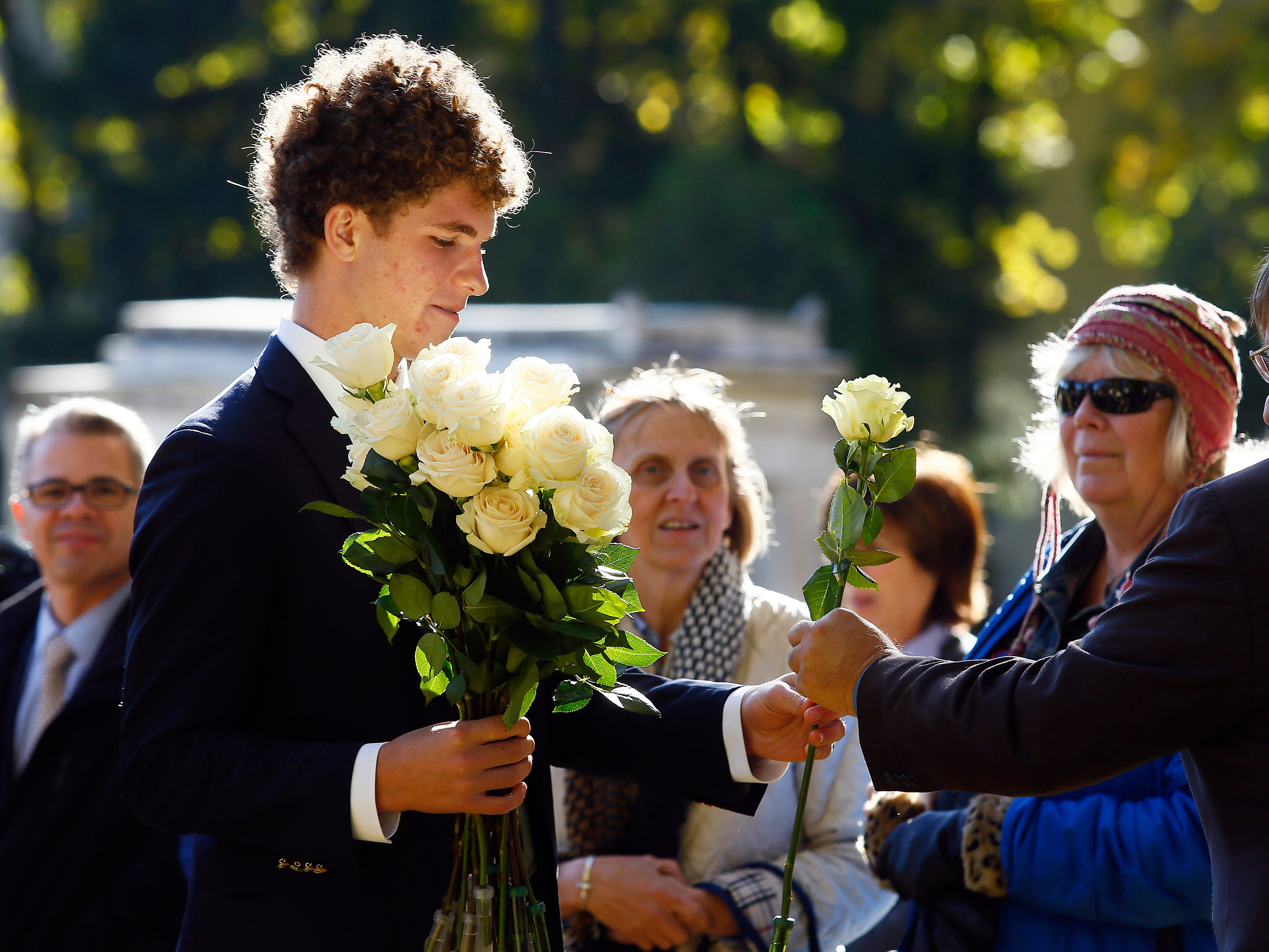 Delbarton junior Jack Readlinger, l, hands out roses to classmates during a graveside service and blessing at Orchard Street Cemetery in Dover gathering to bless the grave for baby Anthony Mary, whom they so-named after he was abandoned and found deceased at a recycling center in Mine Hill. October 30, 2018, Dover, NJ
