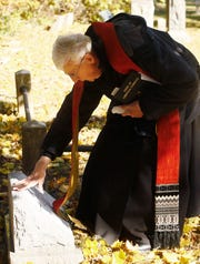 Father Hilary O'Leary OSB blesses the grave of baby Anthony Mary, leading Delbarton students during a graveside service and blessing at Orchard Street Cemetery in Dover for the baby whom they named after he was abandoned and found deceased at a recycling center in Mine Hill. October 30, 2018, Dover, NJ