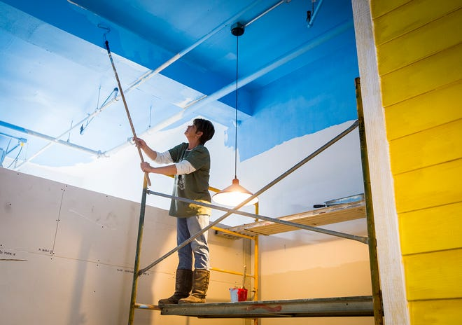 Manager Danielle Woodson paints the ceiling at the future site of the Barking Cow restaurant in downtown Muncie Tuesday afternoon.