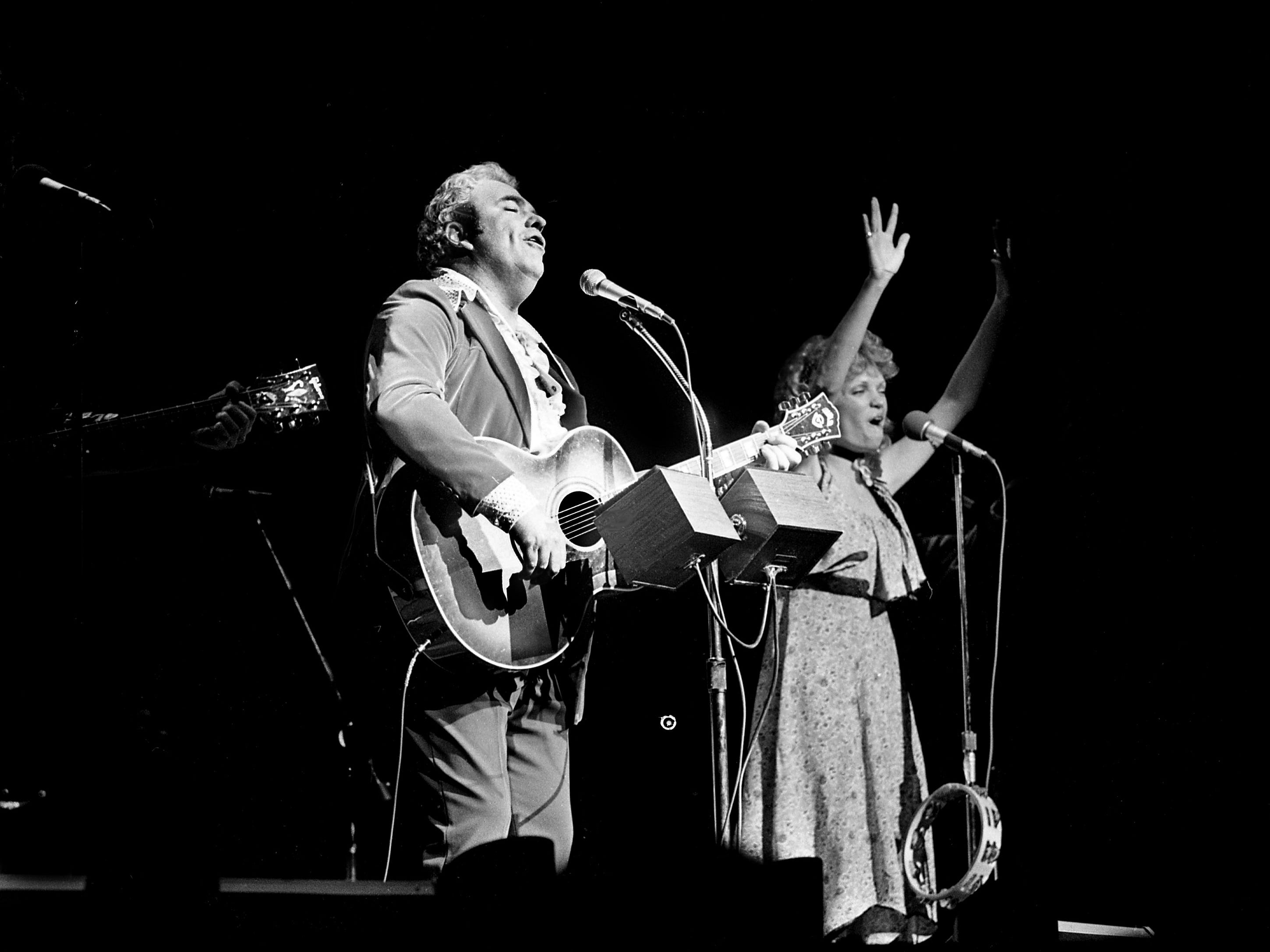 Singer-songwriter Hoyt Axton, left, finishes a song during his Halloween concert at the Grand Ole Opry House on Oct. 31, 1978.