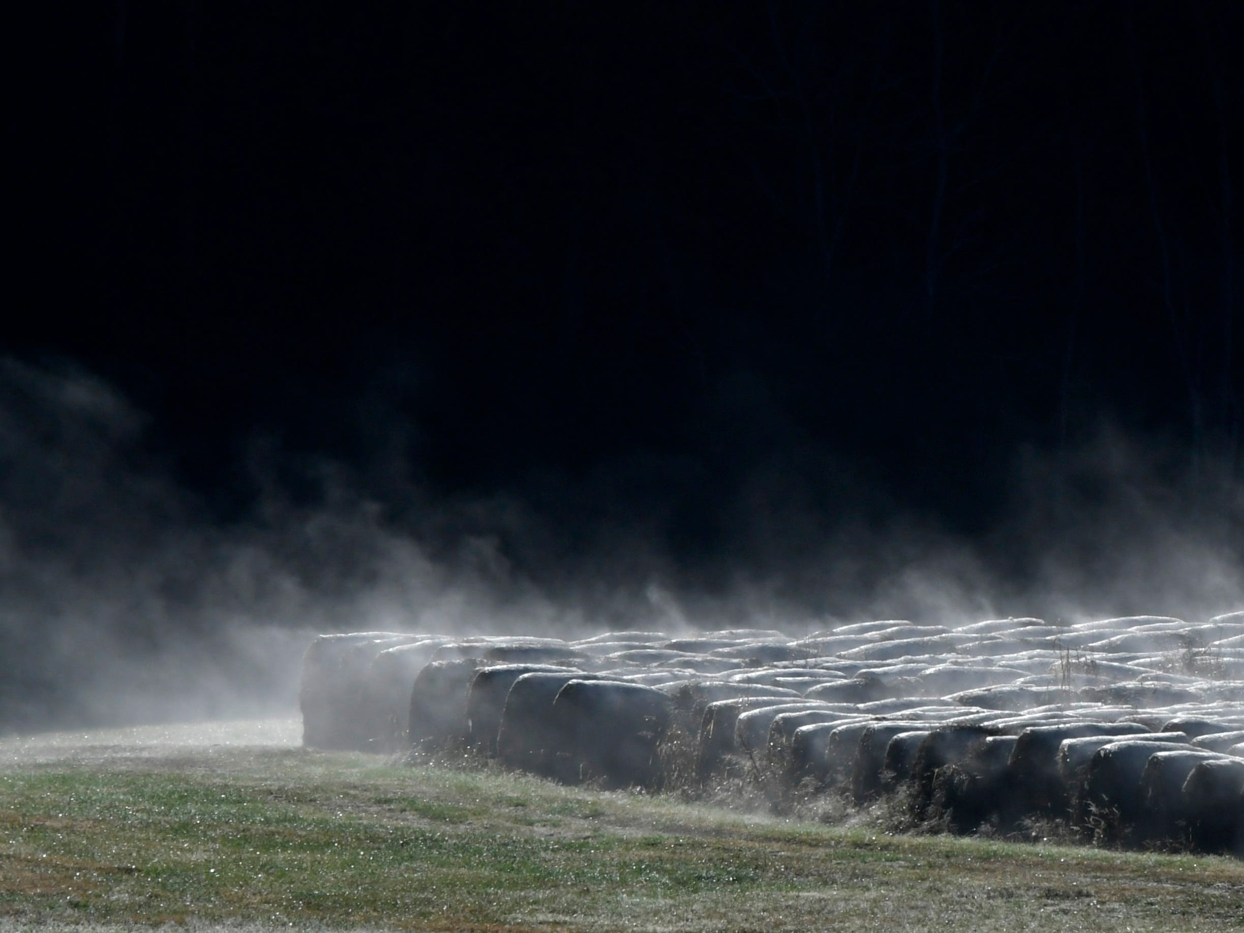 Fog rises from harvest hay rounds on a farm in Boston community in Williamson County l  on Monday, Oct 29, 2018.