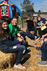Teacher Genny Nash and Sydney Robbins ride together on hay bales at the Poplar Grove Fall Festival on Oct. 11, 2018.
