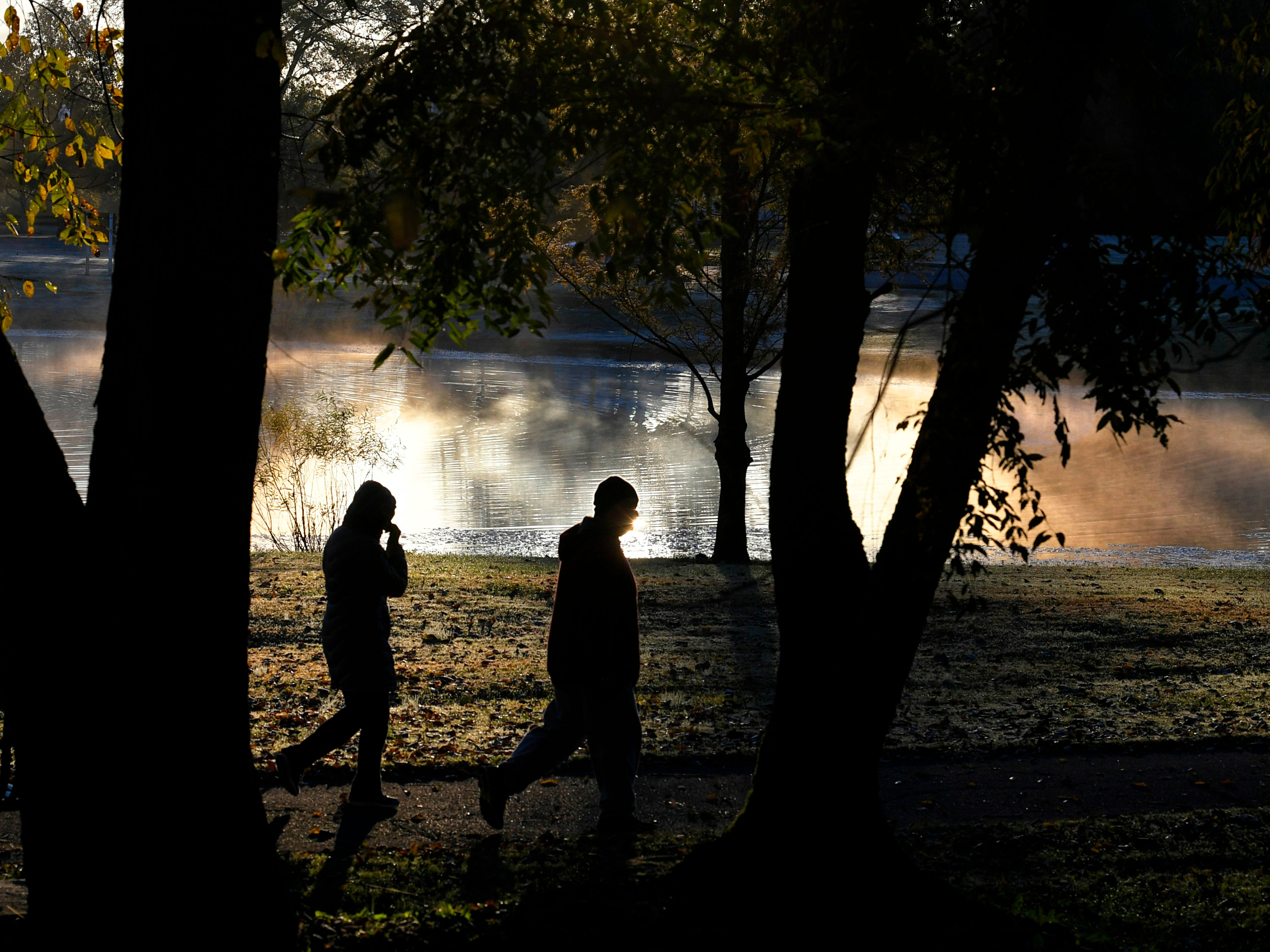 People take a morning walk at Jim Warner Park as fog rises from a pond on Monday, Oct 28, 2018.