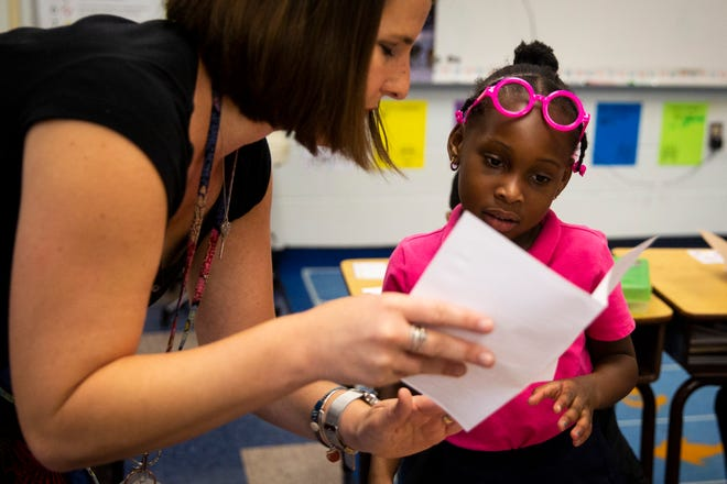 Brittany Crouss helps Janay Campbell, 6, with a thank you card after being presented with a Teachers of Distinction certificate from Champions For Learning on Tuesday, Oct. 30, 2018, at Lely Elementary School in East Naples.
