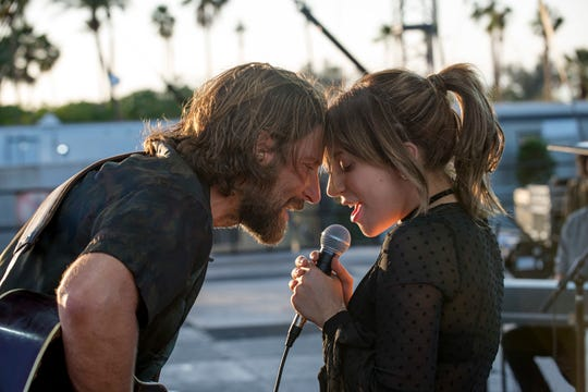 """This image released by Warner Bros. shows Bradley Cooper, left, and Lady Gaga in a scene from the latest reboot of the film, """"A Star is Born."""""""