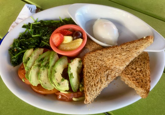 """Noreen's Breakfast"" from Skillets restaurants features steamed spinach, grilled tomato, avocado and a poached egg over wheat toast with a fresh fruit cup."