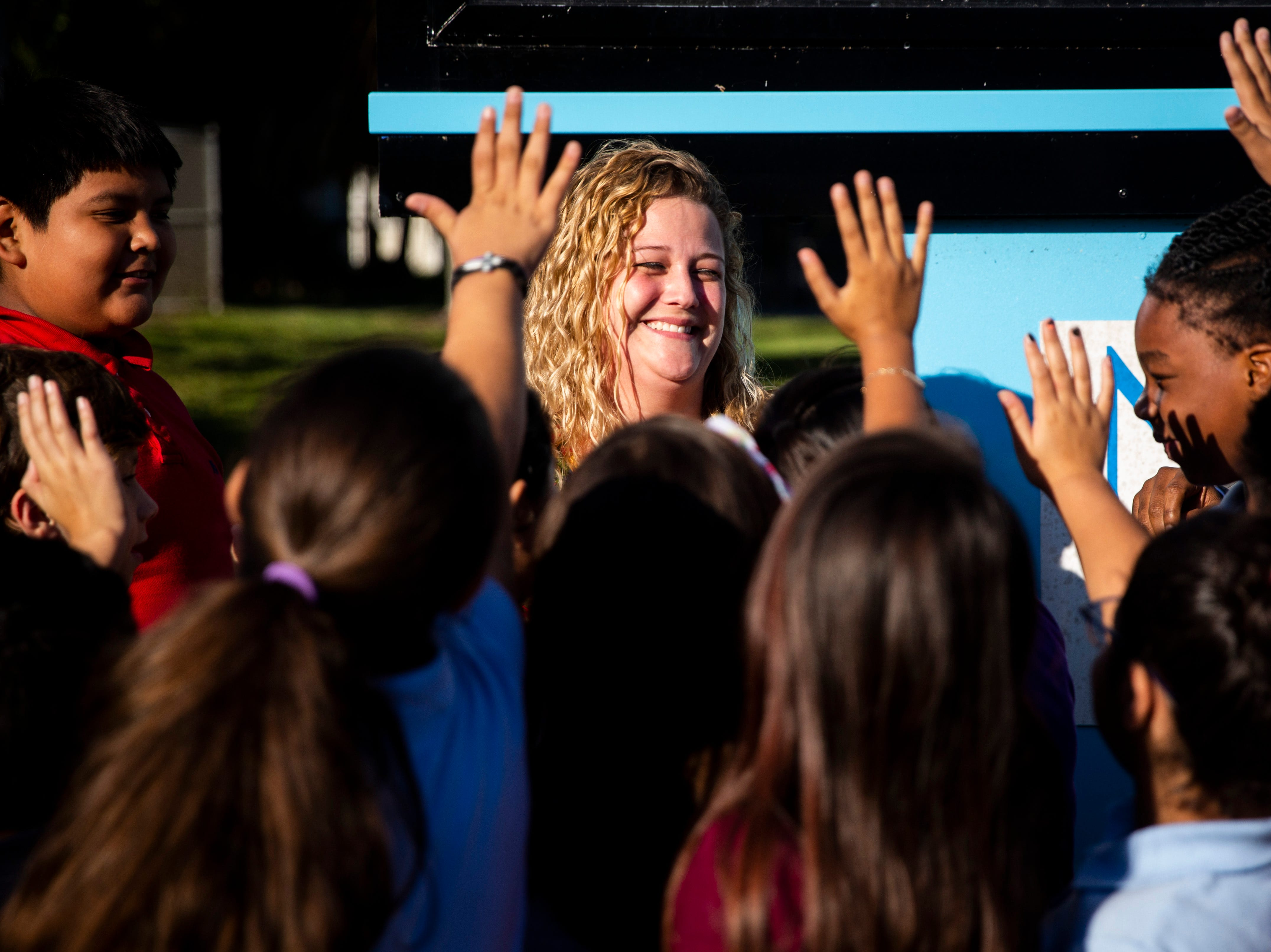 Christine Brady's students crowd around to high-five her after she was presented with a Teachers of Distinction certificate from Champions For Learning on Tuesday, Oct. 30, 2018, at Avalon Elementary School in East Naples.