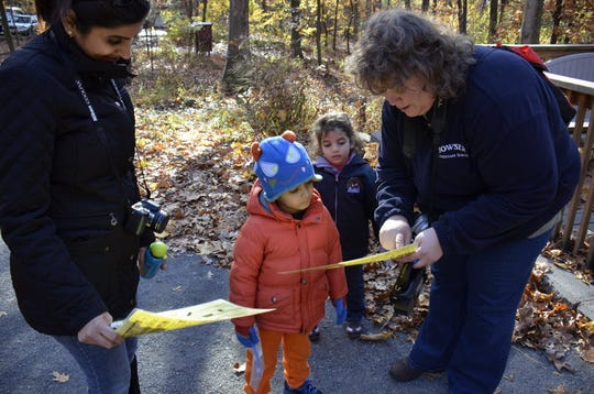 Catalina Hanafy goes over the scavenger hunt check list with Veer Sardana and Zahrah Hanafy, as Veer's mom, Aperna looks on.