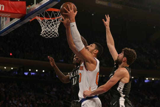 New York Knicks center Enes Kanter (00) shoots against Brooklyn Nets center Ed Davis (17) and Brooklyn Nets guard Joe Harris (12) during the second quarter at Madison Square Garden.