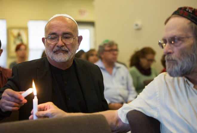 Fred Yellon, right, holds out a candle while Carlos Estrada-Vega lights it during a memorial service for those that were killed in the Saturday attack on the Tree of Life Synagogue in Pittsburgh.  The service was held Monday, Oct. 29, 2018 at Chabad Jewish Center of Las Cruces.
