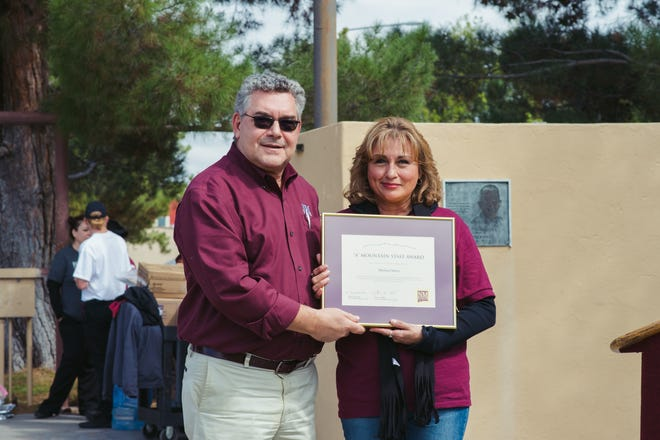 "President Floros of New Mexico State University presents the ""A"" Mountain Staff Award to Maria Theresa Chavez at the employee picnic."