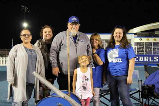 Left to right: Alana Twaddle, Darlene Rushing, Bruce Chitwood, Debbie Chitwood and Mariah Clare in the back row and Ariyah Chitwood in the front pose in front of the Carlsbad cannon. Bruce Chitwood has spent the last decade firing the cannon for Carlsbad at home games and brings his family to enjoy the games.