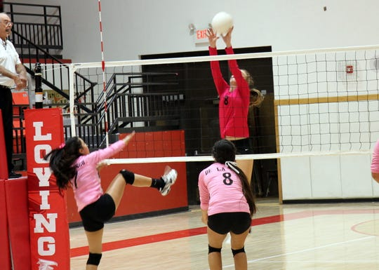Loving's Cydni Ottman (8) blocks a spike attempt during the first set of Monday's game against Hagerman.