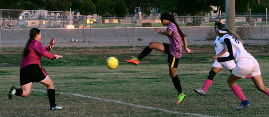Alamogordo Lady Tiger Shawna Williams sends the ball on its way past Deming Lady Wildcat keeper Alissa Cordova for the final goal in a 10-0 rout of the Lady Wildcats, one of four goals Williams scored during the game.