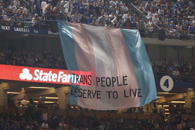 """LOS ANGELES, CA - OCTOBER 28:  A banner with the words """"Trans People Deserve to Live"""" is displayed during Game Five of the 2018 World Series between the Los Angeles Dodgers and the Boston Red Sox at Dodger Stadium on October 28, 2018 in Los Angeles, California.  (Photo by Sean M. Haffey/Getty Images)"""