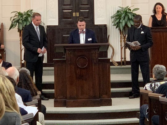 From left to right: Pastor Joey Rogers from the Pace Assembly of God; Rev. Brandon Bures, associate pastor of First United Methodist Church; and Rev. Freddie Tellis of Allen Chapel AME take turns reading prayer during a Tuesday night service at Temple Beth El honoring the victims of the Pittsburgh synagogue shooting.