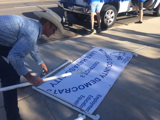 Kelly Lindsey, chairman of the Mohave County Democrats, assembles a sign to be used as the group marches in the London Bridge parade in Lake Havasu City on Saturday, Oct. 27, 2018