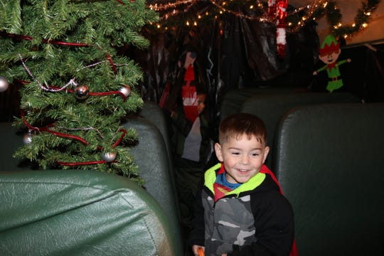 """Cameron Dunson, 4, was all smiles when the haunted school bus at the PCHS """"Spooktacular"""" ended with a surprise Christmas-themed finale."""