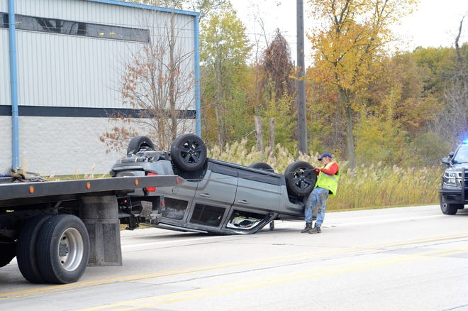 Crews work to remove a flipped Jeep from Busha Highway on Oct. 30, 2018,  in Marysville, Michigan.