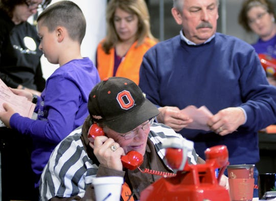 Dr. Daniel Wilhelm, wearing an Ohio State University cap, makes a call during the March Of Dimes Jail and Bail fundraising event. Wilhelm retired in July after 52 years as a pediatrician in the St. Clair County area.