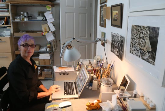 Paola Bari reviews photos from a trip she took to Africa at her home studio in the Town of Poughkeepsie on October 23, 2018.