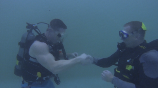 YDR Reporter John Buffone and Dive Master Wayne Mallquist shake hands after completing an underwater drill.