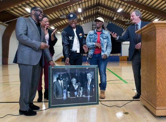 Relatives of Voni Grimes, from the left: the Rev. Oscar Rossum Sr., Casey Rossum, Diaz Woodard and April Collier, receive a proclamation from York Mayor Michael Helfrich, right, while holding a picture of Grimes, on left. In the picture, he is standing with Helen Thackston and George A. Goodling. The relatives participated in the event to mark the conclusion of the the first wave of renovations to the century-old gym.