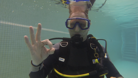 "Dive Master Wayne Mallquist gives the ""OK"" symbol during an underwater training course at the York YMCA."