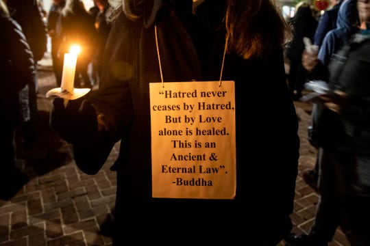 Wearing a Buddha quote around her neck, Cindy Teilazzo holds onto a candle during a candlelight vigil in front of city hall. Hundreds of people gathered for the 'York Vigil against Hate,' mourning the 11 dead from the weekend shooting at Tree of Life synagogue in Pittsburgh.