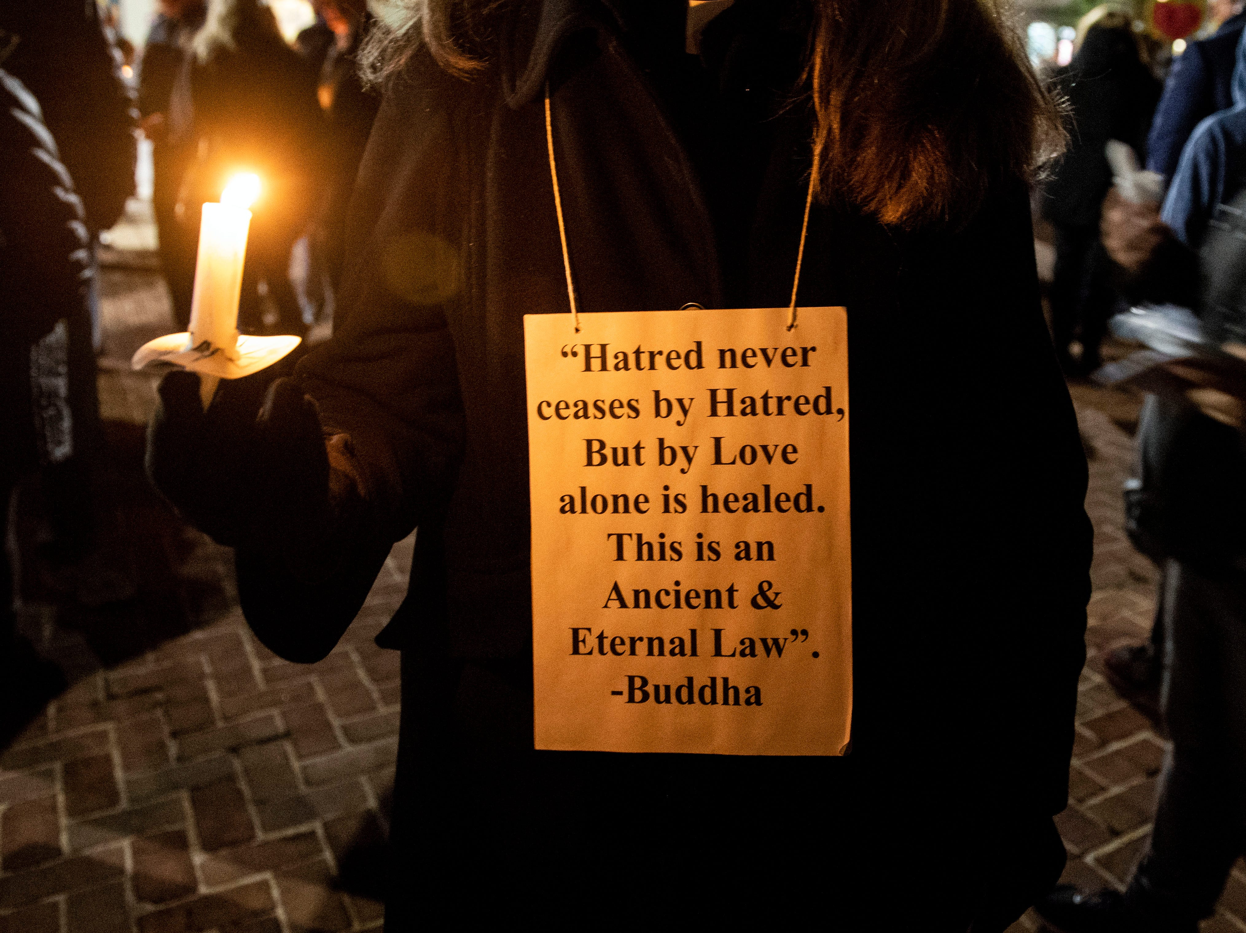 Wearing a Buddha quote around her neck, Cindy Teilazzo holds onto a candle during a candlelight vigil in front of city hall on Monday, Oct. 29, 2018. Hundreds of people gathered for the 'York Vigil against Hate,' mourning the 11 dead from the weekend shooting at Tree of Life synagogue in Pittsburgh.