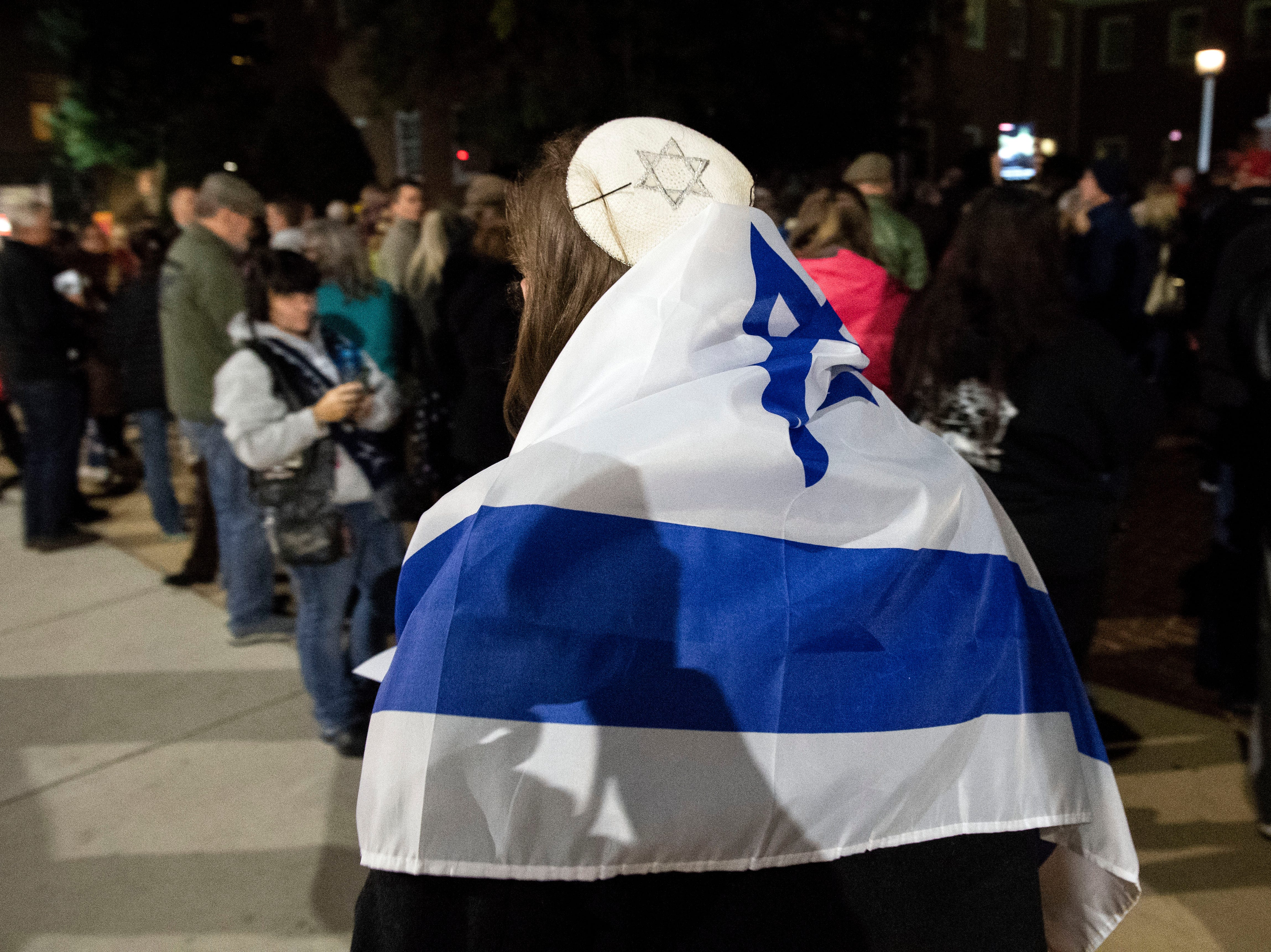 Wrapped in a flag of Israel, John Sutherland walks past a crowd during a candlelight vigil in front of city hall on Monday, Oct. 29, 2018. Hundreds of people gathered for the 'York Vigil against Hate,' mourning the 11 dead from the weekend shooting at Tree of Life synagogue in Pittsburgh.
