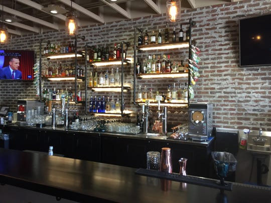 The back bar at Rue Bourbon rises against a brick wall textured to look vintage.