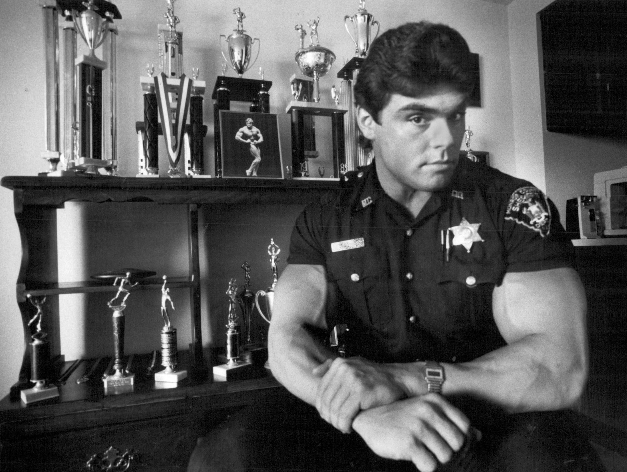 In this 1986 photo, Monroe County Sheriff's Deputy Bob Good flexes his biceps in front of the trophies he had won in amateur body building competitions.
