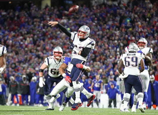 BUFFALO, NY - OCTOBER 29: Tom Brady #12 of the New England Patriots is hit by Lorenzo Alexander #57 of the Buffalo Bills as he throws during NFL game action at New Era Field on October 29, 2018 in Buffalo, New York. (Photo by Tom Szczerbowski/Getty Images)