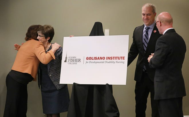 Dr. Dianne Cooney Miner, far left, the founding dean of the Wegmans School of Nursing, hugs Ann Costello, Golisano Foundation director, as they help unveil the name of the new Golisano Institute for Developmental Disability Nursing during a press conference at St. John Fisher College in Pittsford on Tuesday, Oct. 30, 2018.  Dr. Cooney Miner will lead the new Golisano Institute.  Helping to unveil the institute are Gerard Rooney , President of St. John Fisher College, far right, and Drew Boshell, Special Olympics senior vice president, sport and health.
