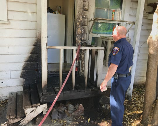 Fire Inspector Patrick O'Connor of the Redding Fire Department investigates a fire Tuesday on a back porch at a residential five-plex on Chestnut Street in downtown Redding.