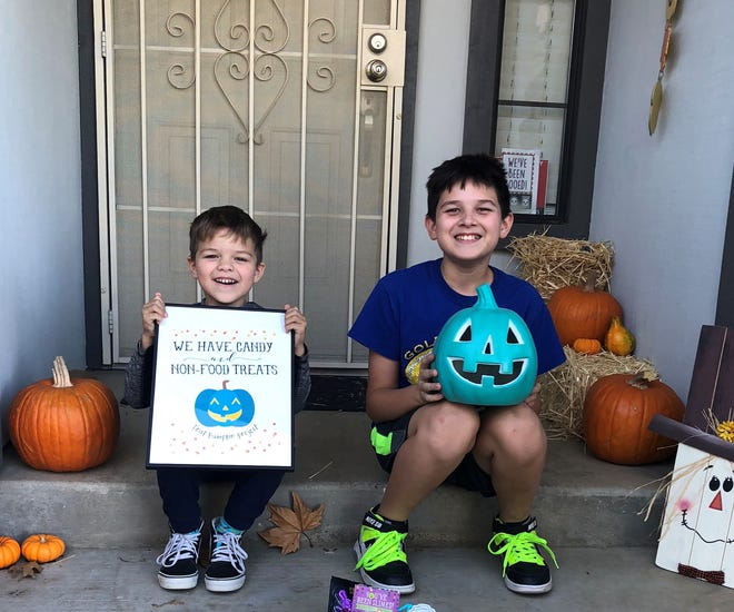 Hunter Mosher, 4, and Logan Mosher, 11, hold up their Teal Pumpkin Project sign and plastic pumpkin light. They plan to place them in front of their door of their Redding home on Halloween to alert trick-or-treaters they have non-edible treats for children with food allergies and other health issues.