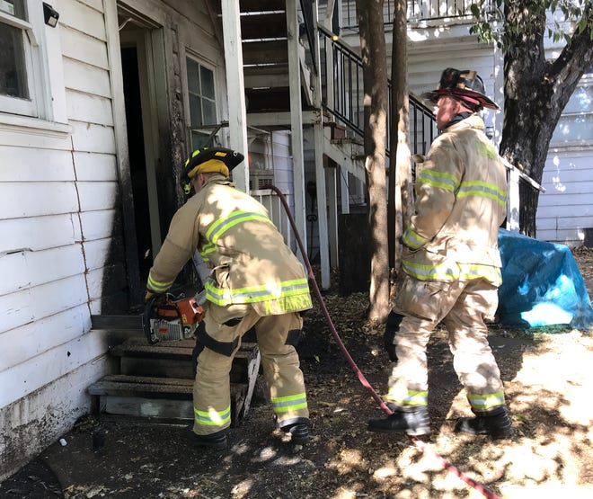 A Redding firefighter uses a chainsaw to open up the wall of a house where a porch caught on fire Tuesday off Chestnut Street in downtown Redding. The fire's cause is under investigation.