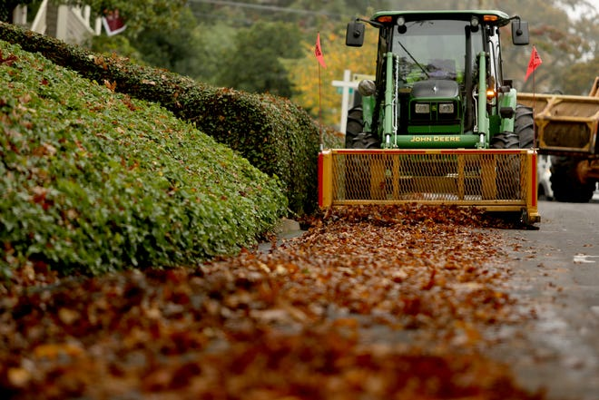 City of Salem workers clean up leaves blocking the street and storm drains in Salem on Tuesday, Oct. 30, 2018.