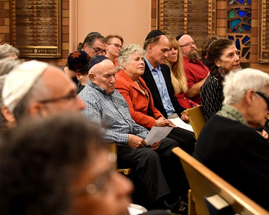 Dr. Norm Jacobson (middle) and his wife Diana Jacobon listen during a special gathering at Temple Beth El on Monday night to mourn those killed in the Pittsburgh synagogue shooting.