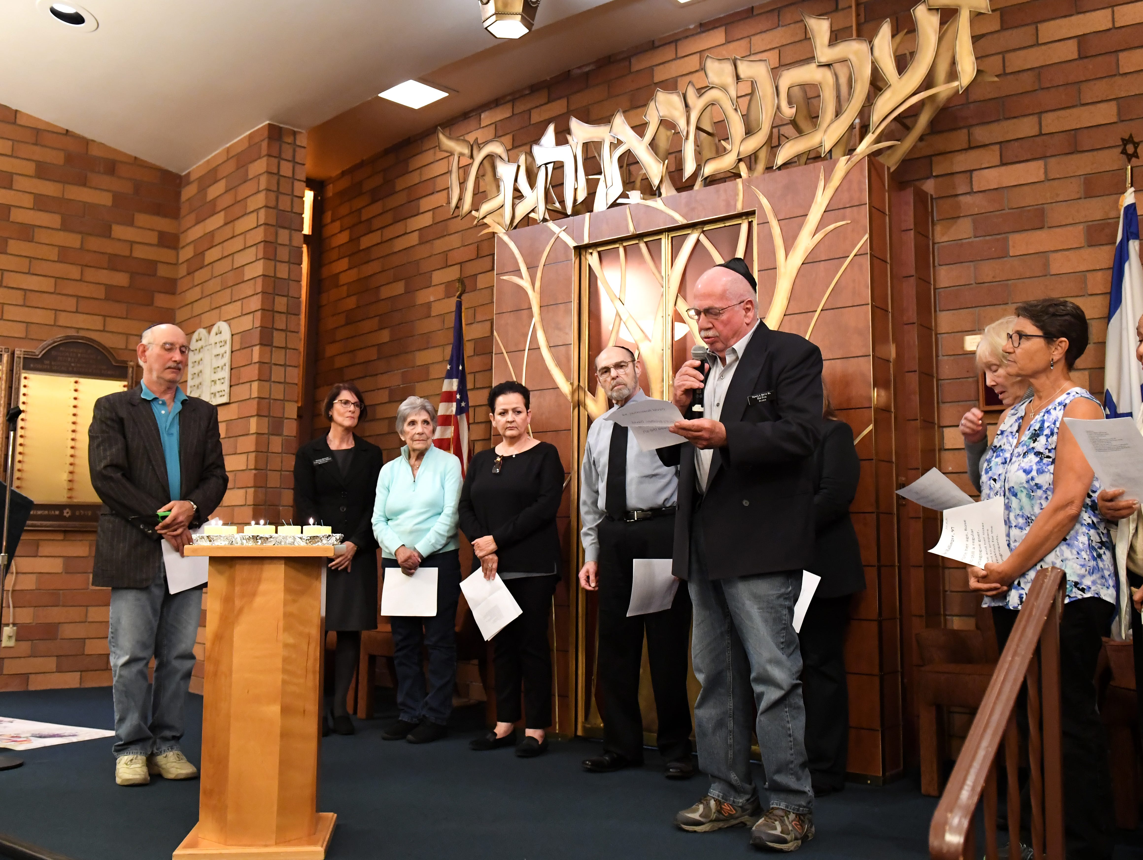 Temple President Hal Peist steps forward to help read the names of each person killed in the Pittsburgh synagogue shooting were read aloud during a special gathering Monday night at Temple Beth El in Salinas.