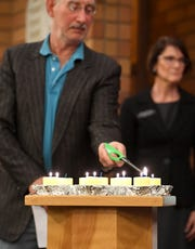 Jeffrey Segal lights the last candle to honor the 11 people killed at a Pittsburgh synagogue Saturday during a special gathering at Temple Beth El.