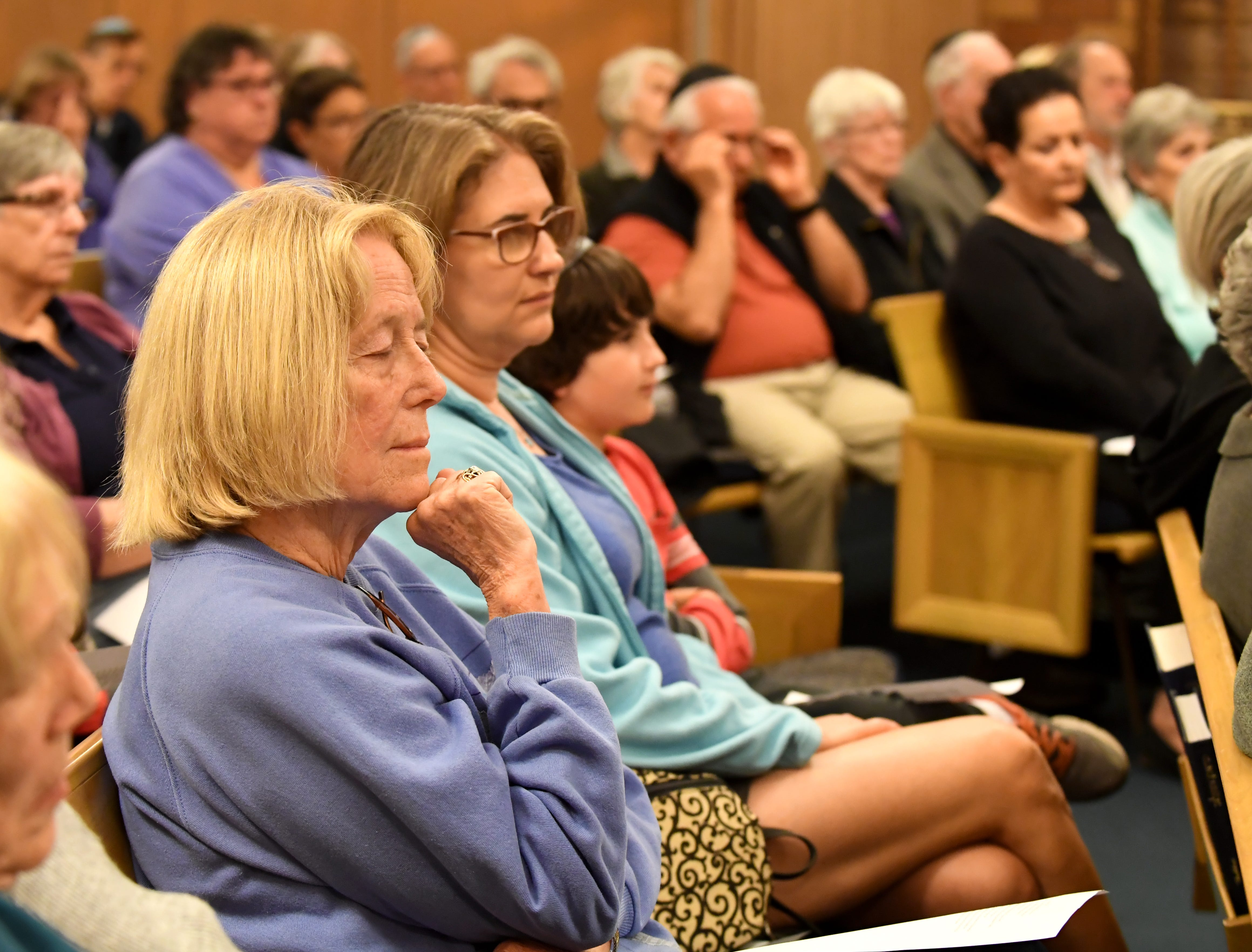 Ginger Bassett (left) of First United Methodist Church closes her eyes during a gathering at Temple Beth El on Monday to mourn those killed at a Pittsburgh synagogue Saturday.
