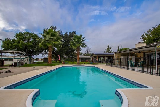This home at 1536 Loop Drive evokes a Florida feel with palm trees and a gorgeous pool. The pool has a dolphin shining through on both ends.