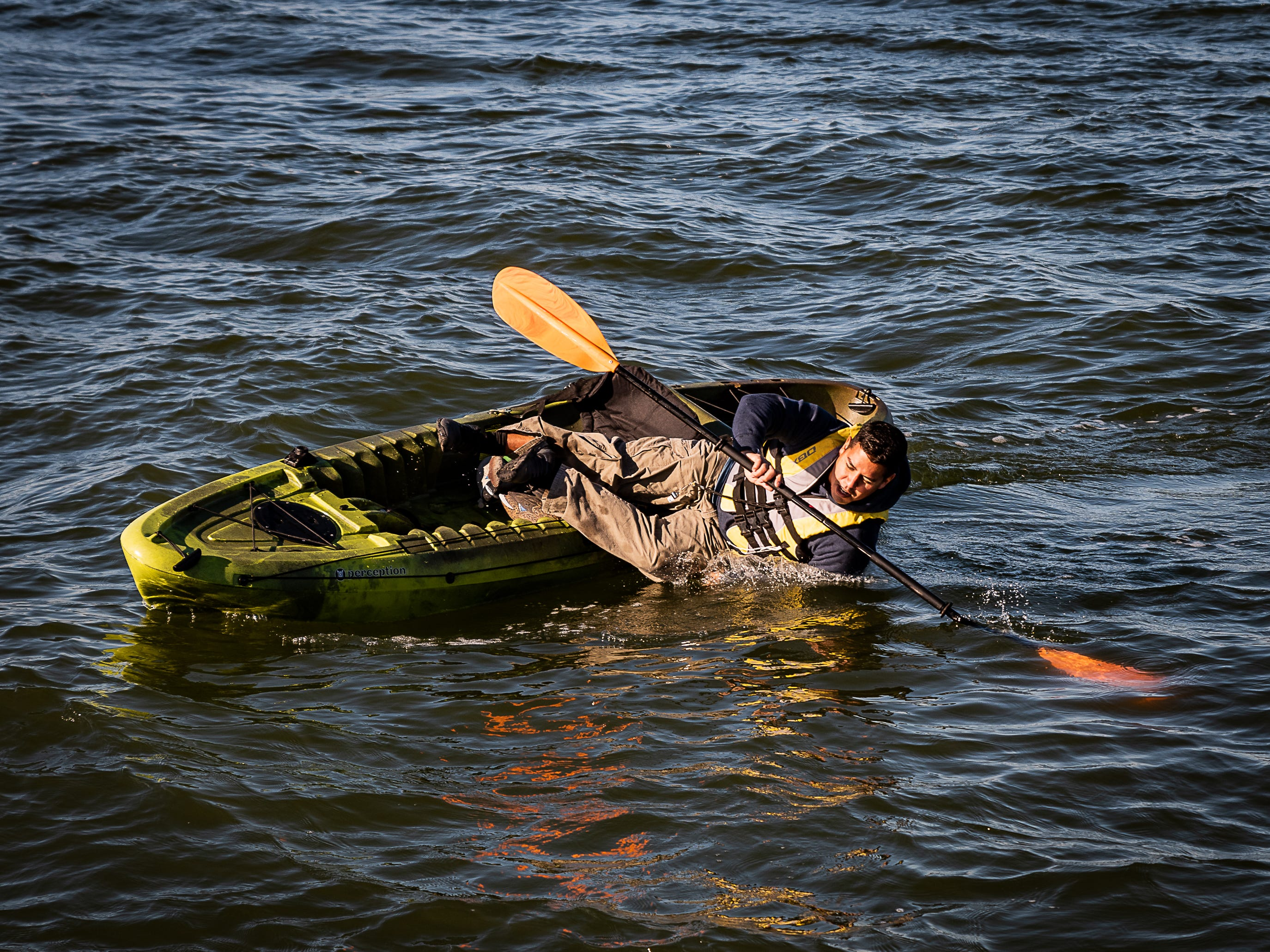 Petty Officer 1st Class Jose Termini falls into the water on purpose to demonstrate proper cold-water survival techniques during a Tuesday, Oct. 30, 2018 U.S. Coast Guard demonstration in Cape Charles, Virginia.