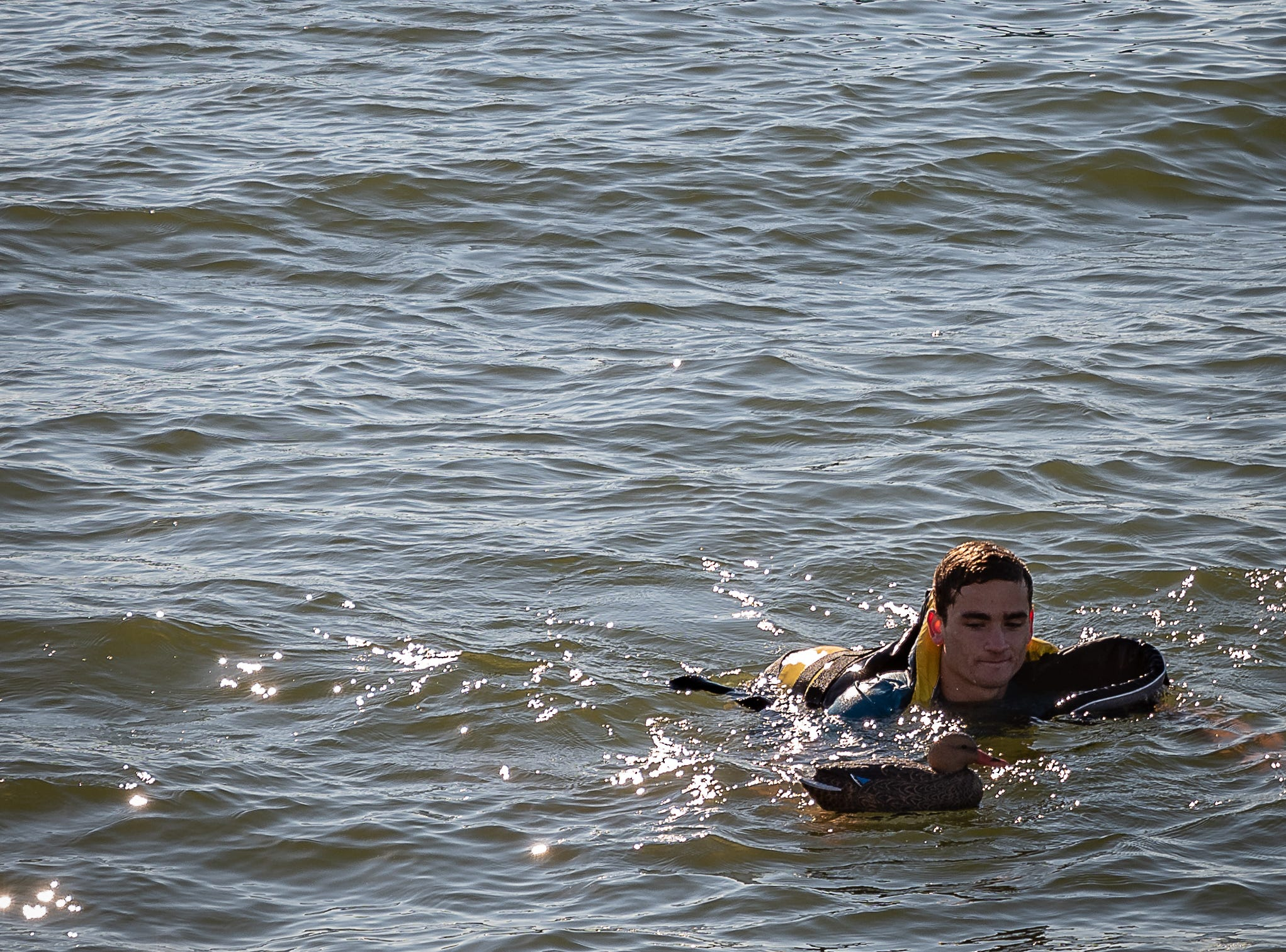 A Coast Guard member swims in the water at Cape Charles Harbor during the demonstration of cold-water survival techniques on Tuesday, Oct. 30, 2018.